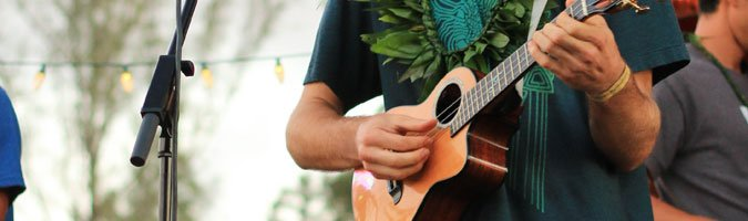 fingerpicking ukulele with lei