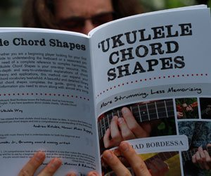 man reading ukulele chord shapes